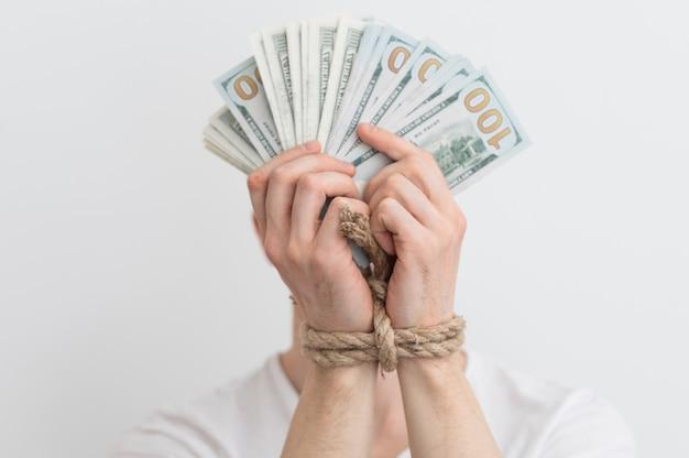 Um homem com as mãos amarradas segurando dólares, dependência de dinheiro, reembolsos, crédito, atrasos