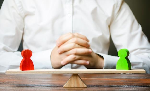 Um homem com as mãos na fechadura e olha para a balança com figuras verdes e vermelhas