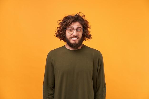 Um homem com barba de óculos e cabelo escuro encaracolado olhando para a frente, lábio mordido, confuso