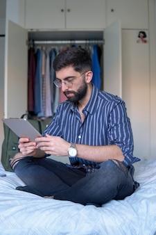 Um homem com barba e camisa listrada na cama em seu quarto usando um tablet