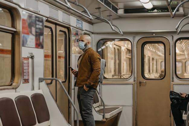 Um homem com barba e máscara facial para evitar a propagação do coronavírus aguarda nova parada em um vagão do metrô. um careca com uma máscara cirúrgica contra covid-19 está segurando um celular em um trem do metrô.