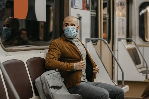 Um homem com barba e máscara médica no rosto para evitar a propagação do coronavírus está em um vagão do metrô. um cara careca com uma máscara cirúrgica contra covid-19 está sentado em um trem do metrô.