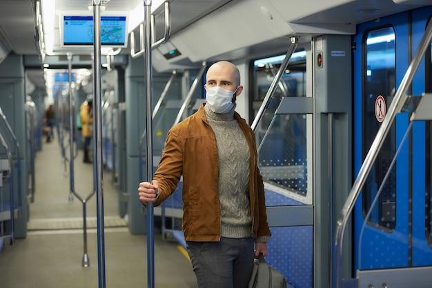 Um homem com barba e máscara médica para evitar a propagação do coronavírus está andando e segurando o corrimão em um vagão do metrô