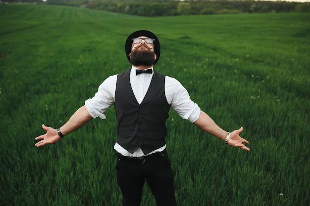Um homem com barba e óculos escuros caminhando no campo