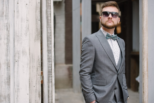 Um homem com barba e óculos escuros em um terno cinza posa na rua para anunciar roupas masculinas.
