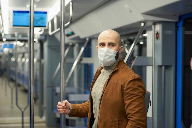 Um homem com barba e uma máscara facial médica para evitar a disseminação de covid-19 está de pé e segurando o corrimão em um vagão do metrô