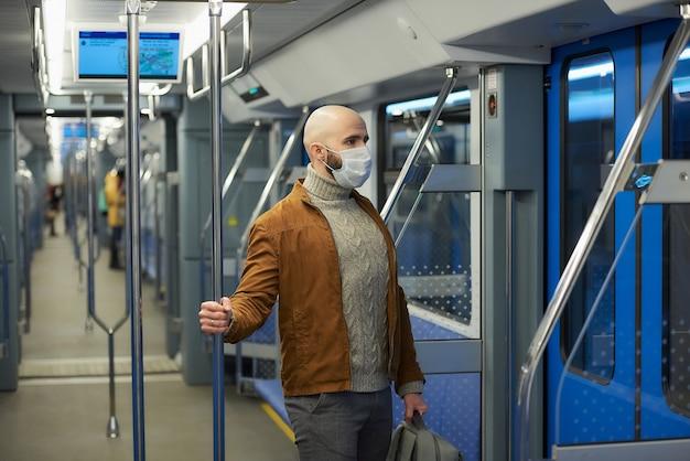 Um homem com barba e uma máscara médica para evitar a propagação do coronavírus está em um vagão de metrô moderno