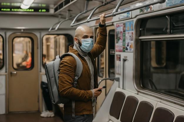 Um homem com barba e uma máscara médica para evitar a propagação do coronavírus está olhando em volta em um vagão do metrô. um careca com uma máscara cirúrgica contra covid-19 está segurando um celular em um trem do metrô.