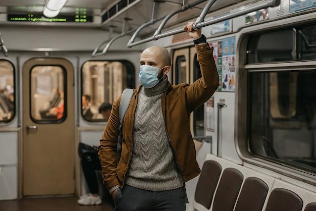 Um homem com barba e uma máscara médica para evitar a propagação do coronavírus está segurando o corrimão em um vagão do metrô. um careca com uma máscara cirúrgica contra covid-19 está em um trem do metrô.