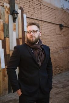 Um homem com barba em um casaco quente preto com um lenço posa para anunciar roupas masculinas no inverno. anuncie roupas masculinas