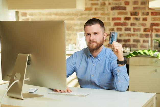 Um homem com barba em uma camisa azul posando com seu cartão de crédito na frente do computador em casa