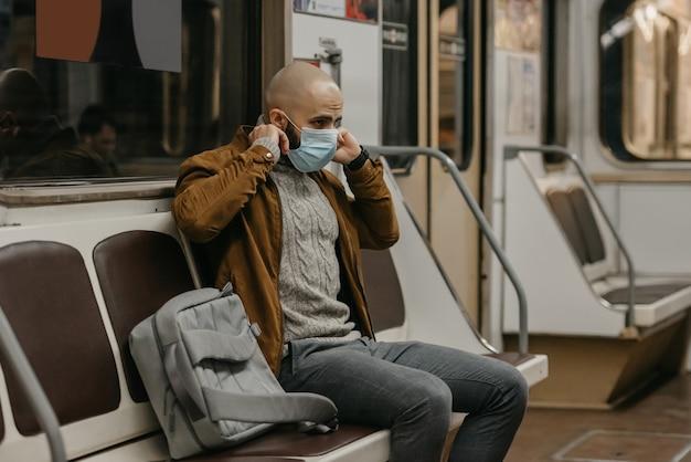 Um homem com barba está colocando uma máscara médica no rosto para evitar a propagação do coronavírus em um vagão do metrô. um cara careca com uma máscara cirúrgica contra covid-19 está sentado em um trem do metrô.
