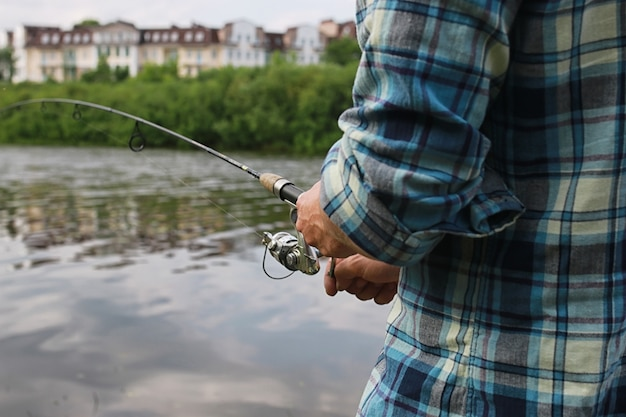 Um homem com barba está pescando para fiar no rio