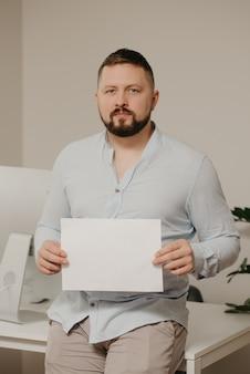 Um homem com barba está sentado com uma folha de papel em branco perto de um computador desktop de aço em casa