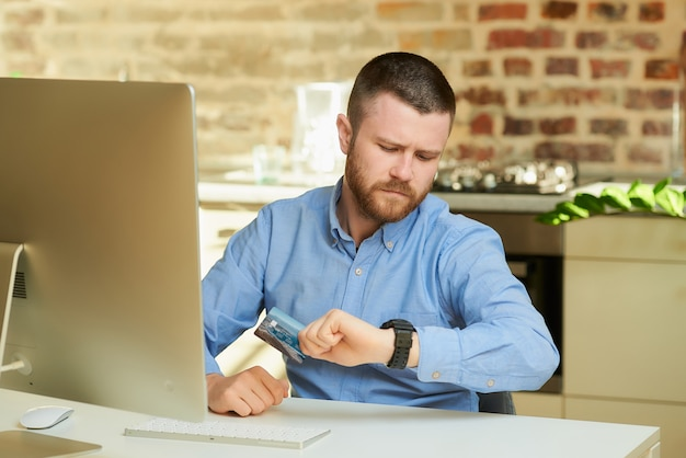 Um homem com barba faz uma careta e segura um cartão de crédito olhando para o relógio de pulso em casa