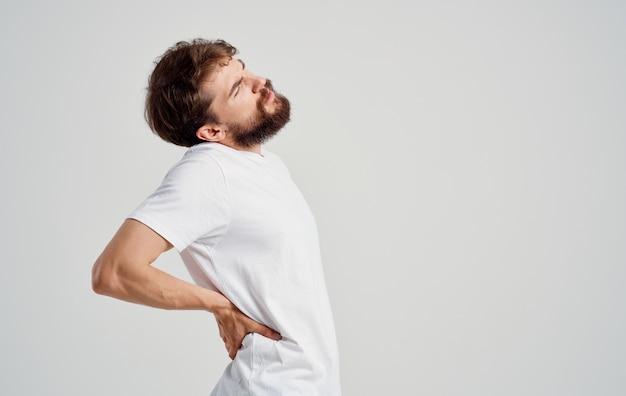 Um homem com barba gesticulando com as mãos dor nas costas, carga na coluna, peso