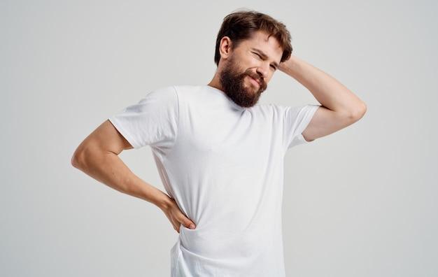 Um homem com barba gesticulando com as mãos dor nas costas carga na coluna