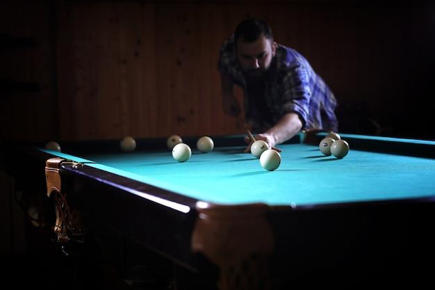 Um homem com barba joga um grande bilhar. festa na piscina de 12 pés. bilhar no jogo do clube para homens. um homem com um taco quebra a pirâmide.