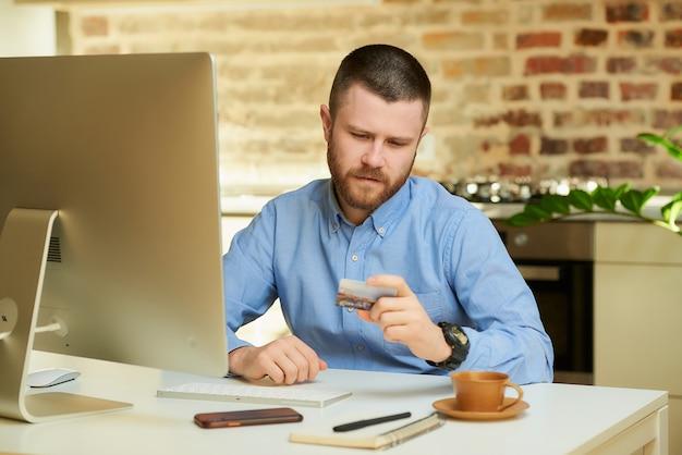 Um homem com barba lê um código de cartão de crédito para fazer compras on-line em casa.