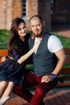 Um homem com barba se senta em um banco com uma linda mulher
