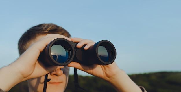 Um homem com binóculos modernos contra o céu e a floresta verde. o conceito de caça, viagens e recreação ao ar livre. banner com espaço de cópia. um viajante ou caçador está observando com binóculos.