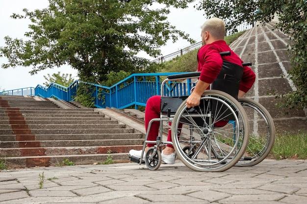 Um homem com deficiência está sentado em uma cadeira de rodas em frente à escada. o conceito de cadeira de rodas, pessoa com deficiência, vida plena, paralítico, pessoa com deficiência, cuidados de saúde, solidão.