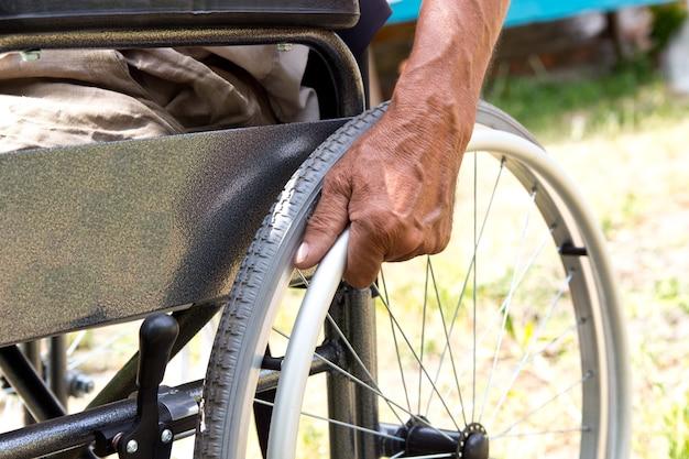 Um homem com deficiência está sentado em uma cadeira de rodas