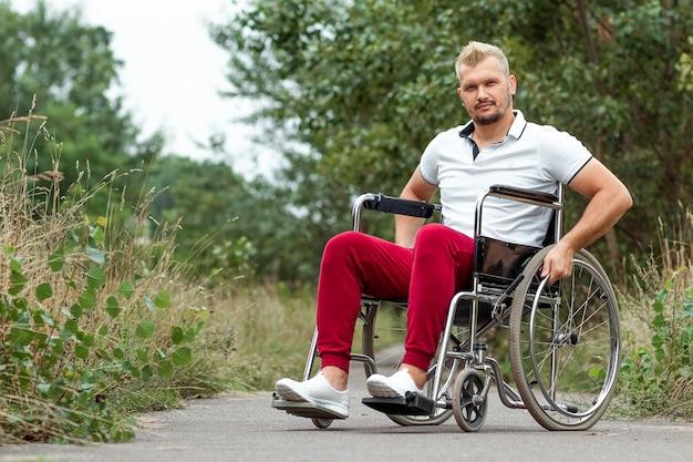 Um homem com deficiência se senta em uma cadeira de rodas na rua. o conceito de cadeira de rodas, pessoa com deficiência, vida plena, paralítico, pessoa com deficiência, cuidados de saúde.