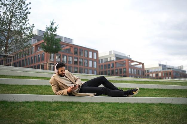 Um homem com fones de ouvido e smartphone ao ar livre no parque da cidade, descansando.