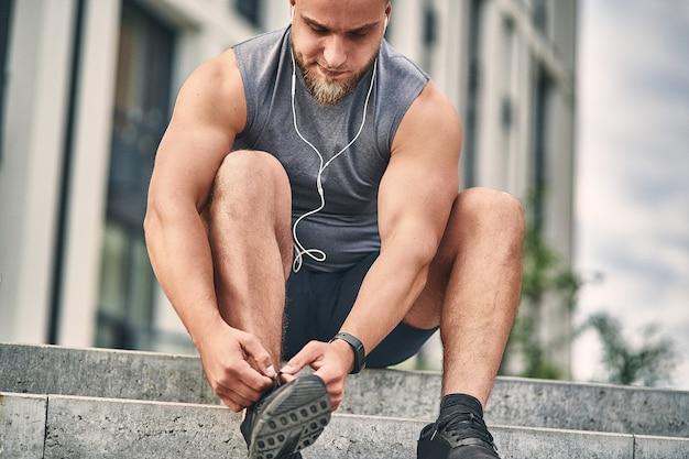 Um homem com fones de ouvido e um uniforme leve e atlético amarra um cadarço em um tênis para correr