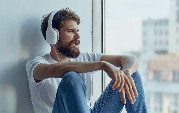 Um homem com fones de ouvido está sentado no parapeito da janela e ouve uma imitação de música ao dirigir um carro
