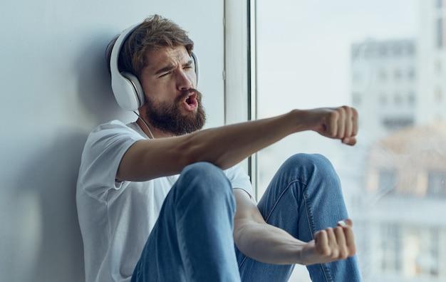 Um homem com fones de ouvido está sentado no parapeito da janela e ouve uma imitação de música dirigindo um carro