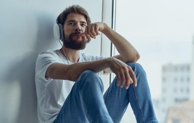 Um homem com fones de ouvido está sentado no parapeito da janela e ouve uma imitação de música dirigindo um volante de carro studio