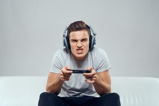 Um homem com fones de ouvido está sentado no sofá jogando videogame.