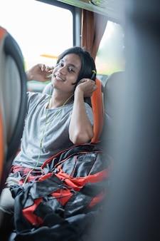 Um homem com fones de ouvido sorri enquanto ouve música enquanto está sentado perto da janela do ônibus