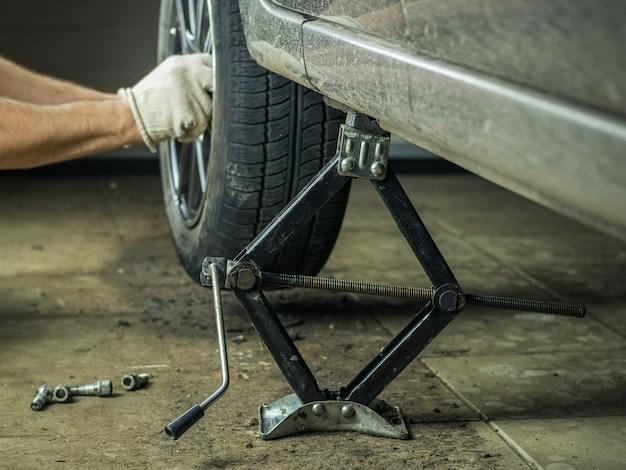 Um homem com luvas para reparar a roda traseira do carro.