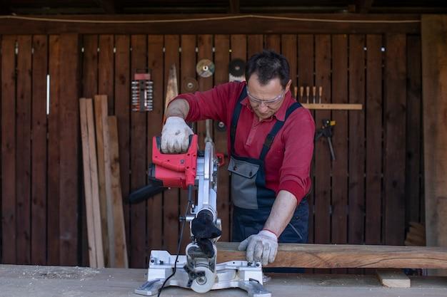 Um homem com macacão de proteção e óculos corta uma viga de madeira com uma serra circular