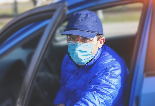 Um homem com máscara médica (respirador) sai de um carro durante uma epidemia