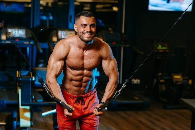 Um homem com músculos na hora do esporte de ginásio