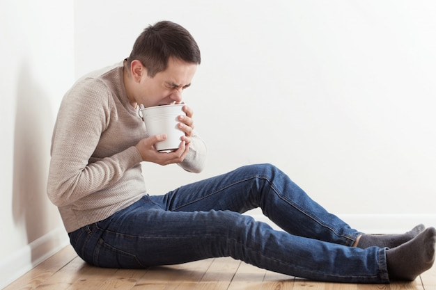 Um homem com náusea no chão