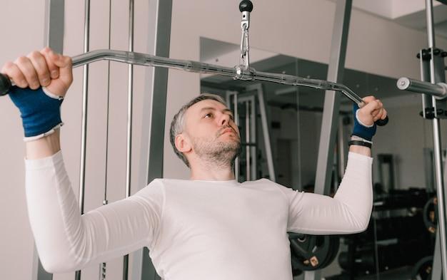 Um homem com o rosto tenso realiza um levantamento terra em um simulador de academia. cuidando do treino intensivo do seu corpo