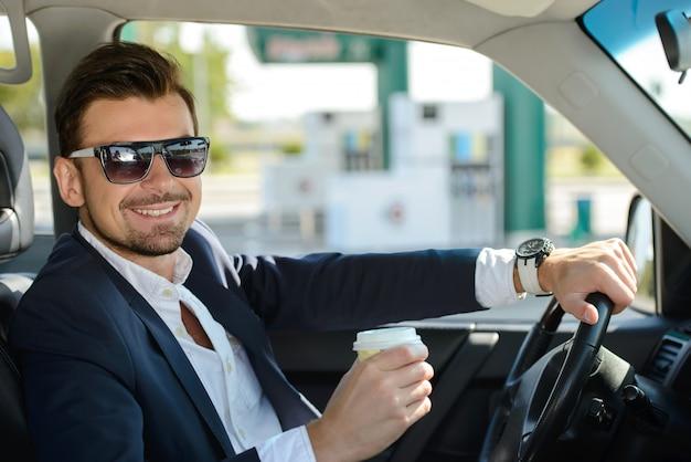 Um homem com óculos está sentado no carro e sorrindo.
