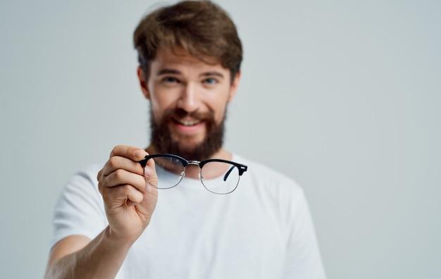 Um homem com óculos na mão problemas de visão dor nos olhos miopia hipermetropia lentes
