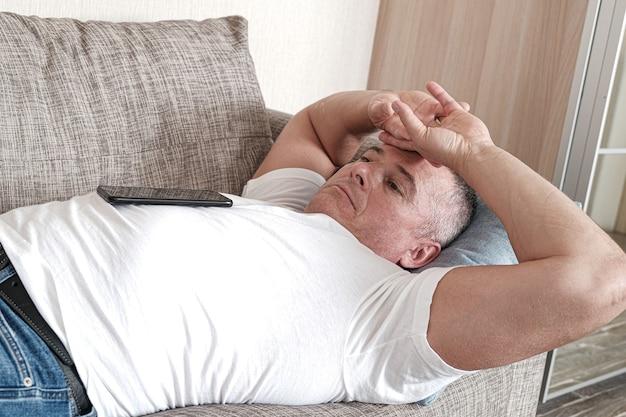 Um homem com olhar distante, deitado no sofá, cruzou as mãos na testa. depressão, saúde precária. estado apático. o conceito de transtorno mental.