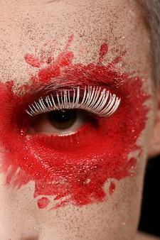 Um homem com olhos e rosto pintados de cor