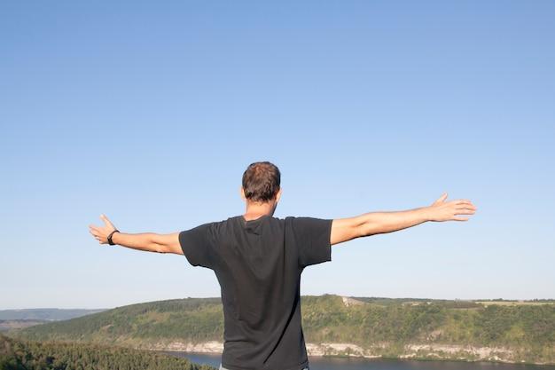 Um homem com os braços estendidos contra o céu e a natureza. recuperação, prazer, conceito de equilíbrio