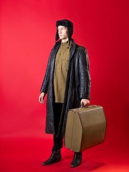 Um homem com roupas antiquadas e um chapéu com protetores de orelha e uma mala grande