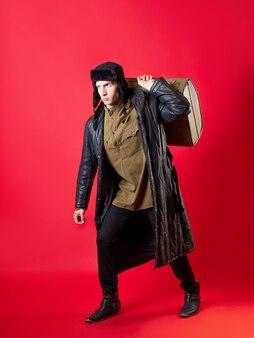 Um homem com roupas antiquadas e um chapéu com protetores de orelha, ele arrasta consigo sua grande mala, ao estilo russo do pós-guerra. retrato em um fundo vermelho