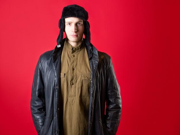 Um homem com roupas antiquadas e um chapéu com protetores de orelha no estilo russo do pós-guerra