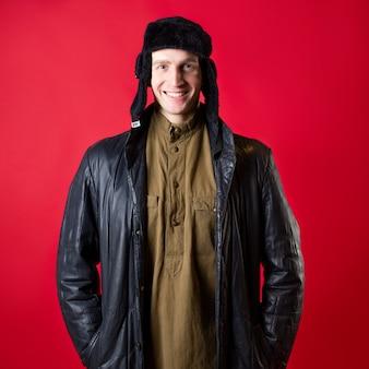 Um homem com roupas antiquadas e um chapéu com protetores de orelha, no estilo russo do pós-guerra.